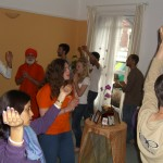 crowded room of many devotees singing around a table